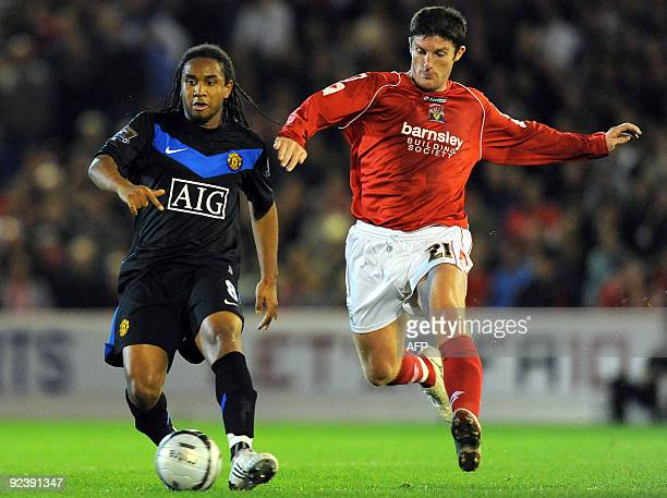 Manchester United's Brazilian midfielder Anderson vies with Barnsley's Irish forward Jon Macken during the Carling Cup fourth round football match at...