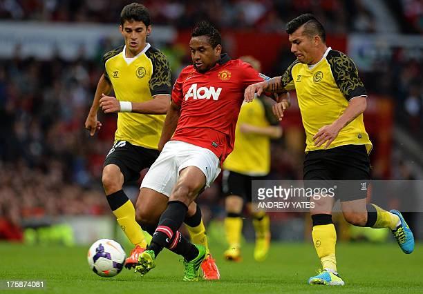 Manchester United's Brazilian midfielder Anderson vies with Sevilla's Argentinian midfielder Diego Perotti and Sevilla's Chilean midfielder Gary...