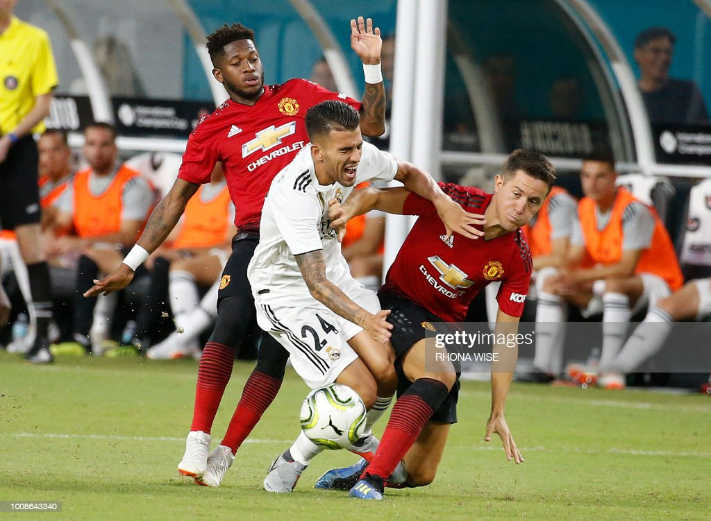 Manchester United's Brazilian midfielder Fred (L) and Spanish midfielder Ander Herrera (R) fight for the ball with Real Madrid's Spanish midfielder Daniel Ceballos during their International Champions Cup friendly football match at Hard Rock Stadium in Miami, Florida, on July 31, 2018.