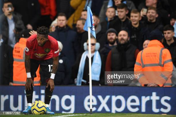 Manchester United's Brazilian midfielder Fred tries to take a corner kick after being pelted with objects from the crowd during the English Premier...