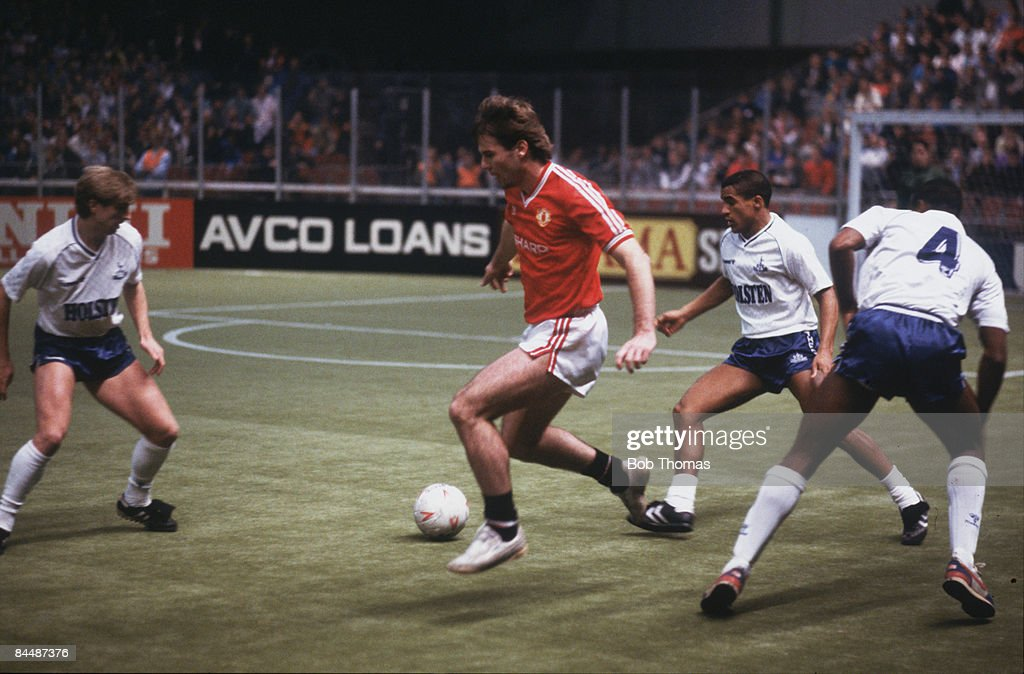 Manchester United's Brian McClair (centre) takes on Tottenham Hotspur defenders during the Guinness Soccer Six Championships at the GMEX centre (now Manchester Central), Manchester, 7th-9th December 1987.