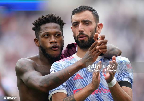 Manchester United's Bruno Fernandes and Fred applaud the fans after the final whistle during the Premier League match at the London Stadium, London....