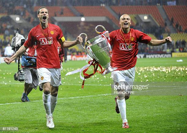 Manchester United's captain Rio Ferdinand and Wes Brown run with the trophy after beating Chelsea in the final of the UEFA Champions League football...