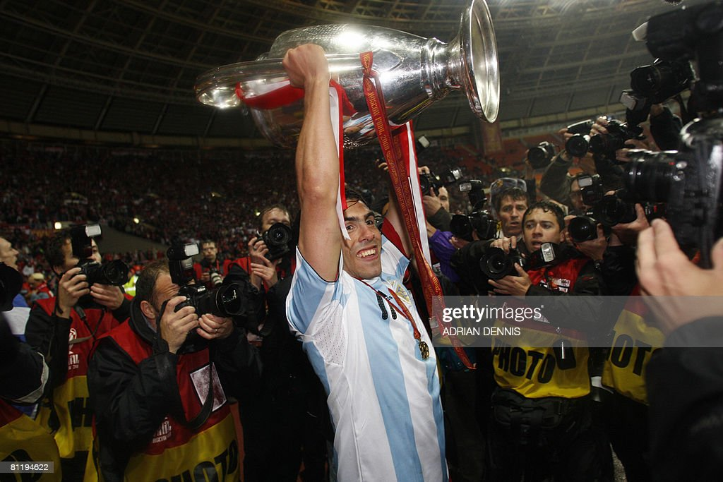 Manchester United's Carlos Tevez celebrates with the trophy after beating Chelsea in the final of the UEFA Champions League football match against Manchester United at the Luzhniki stadium in Moscow on May 21, 2008. The match remained at a 1-1 draw and Manchester won on penalties after extra time. AFP PHOTO / Adrian Dennis