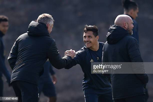Manchester United's Chilean forward Alexis Sanchez shakes hands with Manchester United's Norwegian manager Ole Gunnar Solskjaer during a training...