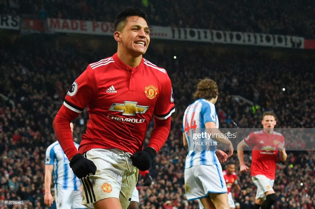 TOPSHOT - Manchester United's Chilean striker Alexis Sanchez celebrates scoring their second goal during the English Premier League football match between Manchester United and Huddersfield Town at Old Trafford in Manchester, north west England, on February 3, 2018. / AFP PHOTO / PAUL ELLIS / RESTRICTED TO EDITORIAL USE. No use with unauthorized audio, video, data, fixture lists, club/league logos or 'live' services. Online in-match use limited to 75 images, no video emulation. No use in betting, games or single club/league/player publications. /