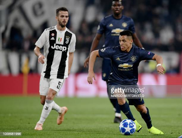 Manchester United's Chilean striker Alexis Sanchez controls the ball next to Juventus' Bosnian midfielder Miralem Pjanic during the UEFA Champions...