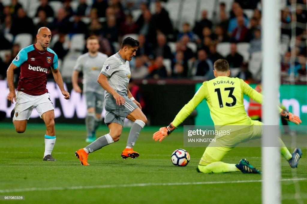 Manchester United's Chilean striker Alexis Sanchez (C) runs the ball around West Ham United's Spanish goalkeeper Adrian (R), but fails to score during the English Premier League football match between West Ham United and Manchester United at The London Stadium, in east London on May 10, 2018. (Photo by Ian KINGTON / AFP) / RESTRICTED TO EDITORIAL USE. No use with unauthorized audio, video, data, fixture lists, club/league logos or 'live' services. Online in-match use limited to 75 images, no video emulation. No use in betting, games or single club/league/player publications. /