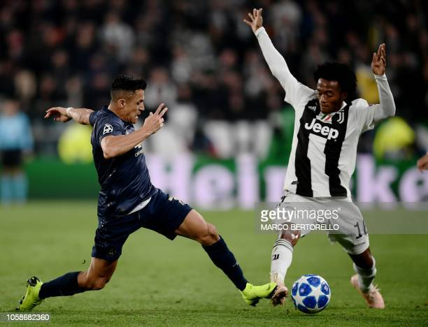 Manchester United's Chilean striker Alexis Sanchez tackles Juventus' Colombian midfielder Juan Cuadrado during the UEFA Champions League group H...
