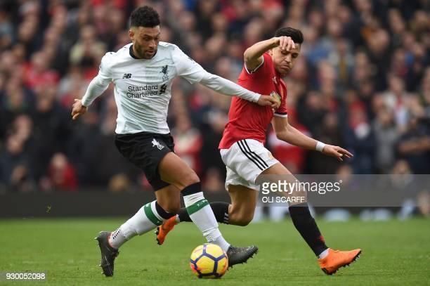 Manchester United's Chilean striker Alexis Sanchez vies with Liverpool's English midfielder Alex OxladeChamberlain during the English Premier League...
