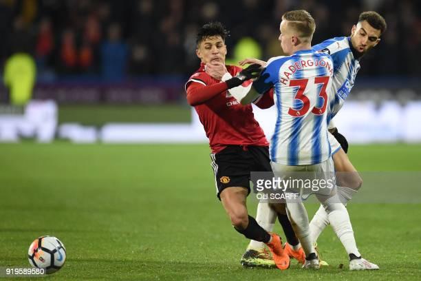 Manchester United's Chilean striker Alexis Sanchez vies with Huddersfield Town's Swiss defender Florent Hadergjonaj and Huddersfield Town's...