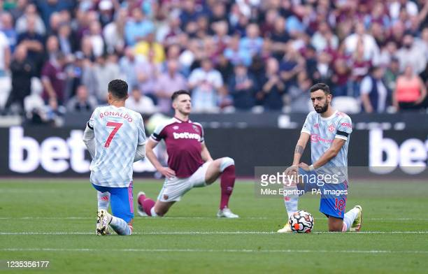Manchester United's Cristiano Ronaldo , Bruno Fernandes and West Ham United's Declan Rice take a knee prior to kick-off during the Premier League...
