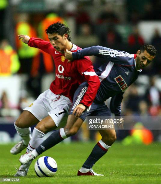Manchester United's Cristiano Ronaldo challenges Benfica's Sabrosa Simao for the ball during the Champions League Group D football match at Old...