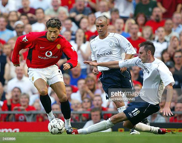 Manchester United's Cristiano Ronaldo takes the ball past Stylianos Giannakopoulos and Nicky Hunt of Bolton Wanderers during the first Premiership...