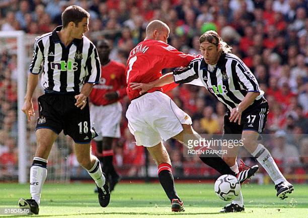 Manchester United's David Beckham fights for the ball with Daniel Cordone of Newcastle as Aaron Hughes looks on Sunday 20 August 2000 during the FA...