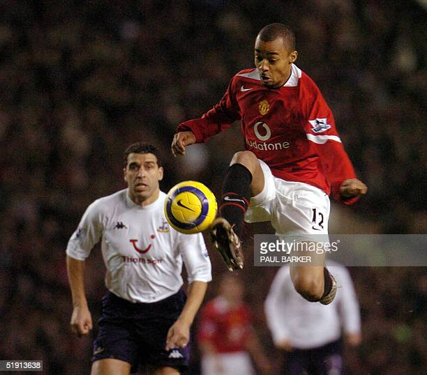 Manchester United's David Bellion vies for the ball with Spurs' Noureddine Naybet during their Premiership football match clash at Old Trafford in...
