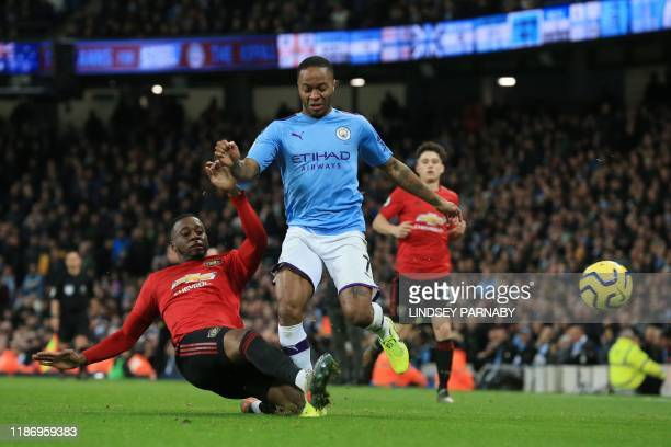 Manchester United's defender Aaron WanBissaka tackles Manchester City's English midfielder Raheem Sterling during the English Premier League football...