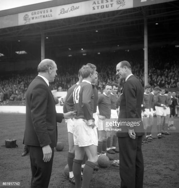 Manchester United's Denis Law gets a prod forward from manager Matt Busby as he is introduced to Prince Philip The Duke of Edinburgh during the team...