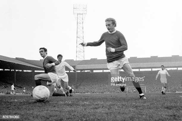 Manchester United's Denis Law tries to keep the ball in play watched by teammate John Aston