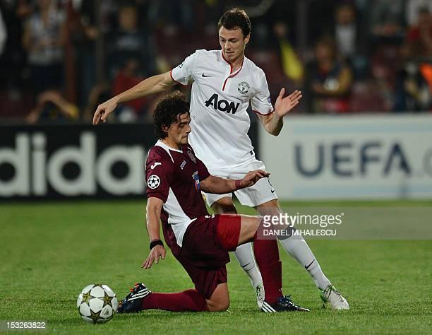 Manchester United's Dutch forward Robin van Persie vies for the ball with CFR Cluj midfielder Matias Aguirregaray during the Champions League Group H...