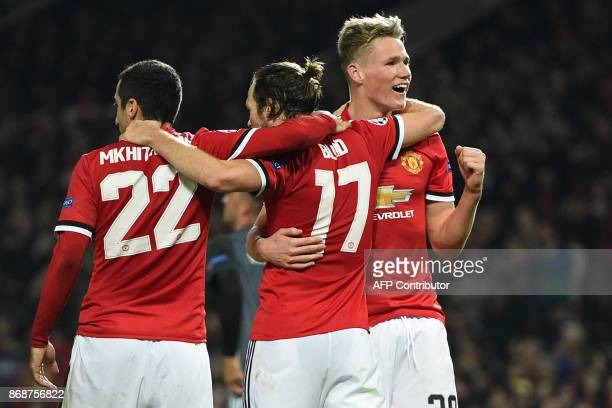 Manchester United's Dutch midfielder Daley Blind celebrates with Manchester United's Armenian midfielder Henrikh Mkhitaryan and Manchester United's...