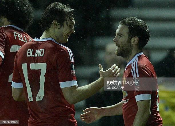 Manchester United's Dutch midfielder Daley Blind congratulates Manchester United's Spanish midfielder Juan Mata for scoring the team's third goal...