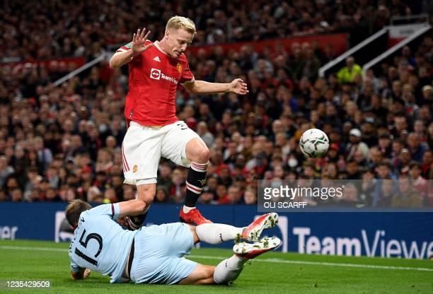 Manchester United's Dutch midfielder Donny van de Beek jumps to avoid West Ham United's English defender Craig Dawson during the English League Cup...