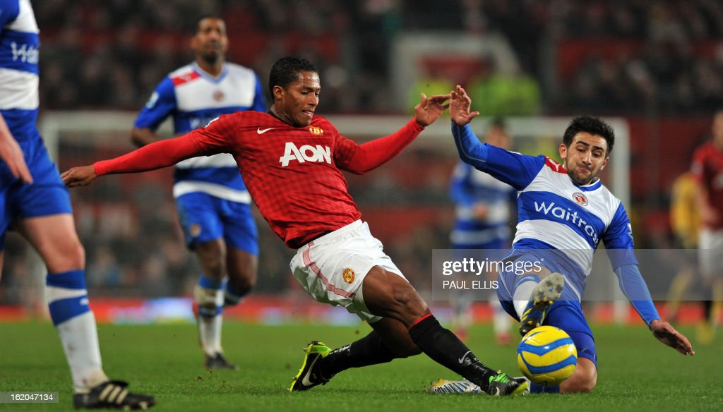 """Manchester United's Ecuador midfielder Antonio Valencia (L) is tackled by Reading's English midfielder Jem Karacan (R) during the English FA Cup fifth round football match between Manchester United and Reading at Old Trafford in Manchester, north west England, on February 18, 2013. USE. No use with unauthorized audio, video, data, fixture lists, club/league logos or """"live"""" services. Online in-match use limited to 45 images, no video emulation. No use in betting, games or single club/league/player publications."""