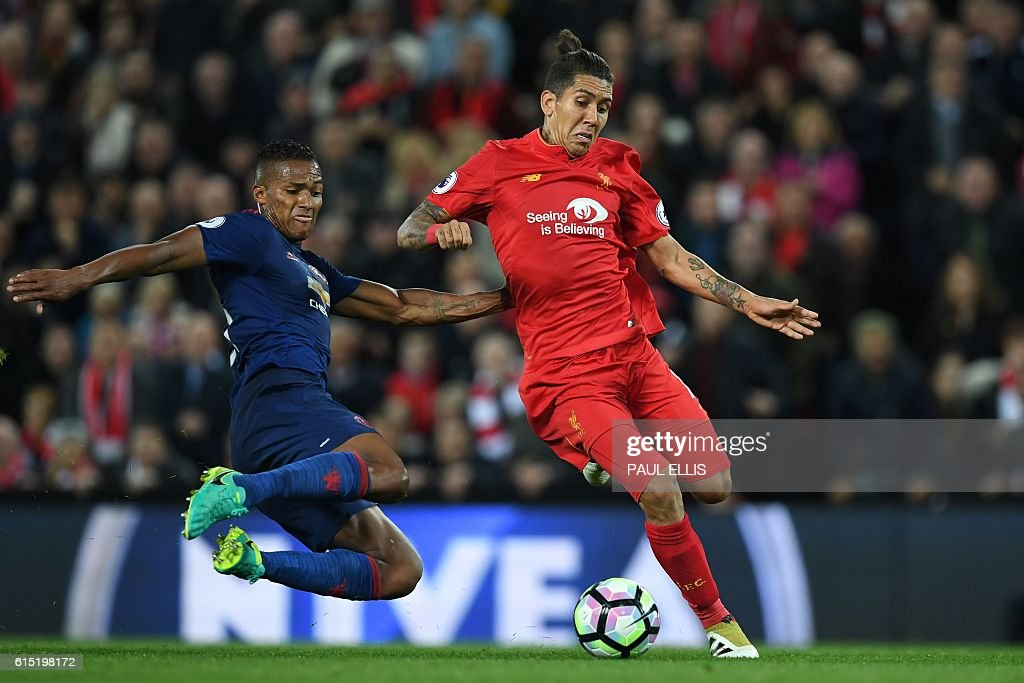 Manchester United's Ecuadorian midfielder Antonio Valencia (L) makes a tackle on Liverpool's Brazilian midfielder Roberto Firmino during the English Premier League football match between Liverpool and Manchester United at Anfield in Liverpool, north west England on October 17, 2016. / AFP / Paul ELLIS / RESTRICTED TO EDITORIAL USE. No use with unauthorized audio, video, data, fixture lists, club/league logos or 'live' services. Online in-match use limited to 75 images, no video emulation. No use in betting, games or single club/league/player publications. /
