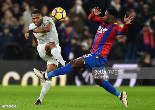 Manchester United's Ecuadorian midfielder Antonio Valencia vies with Crystal Palace's German midfielder Jeffrey Schlupp during the English Premier...