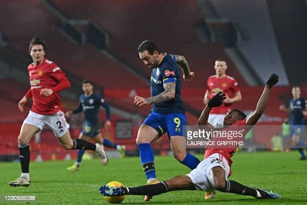 Manchester United's English defender Aaron Wan-Bissaka stretches to make a tackle on Southampton's English striker Danny Ings during the English...