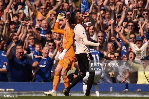 Manchester United's English defender Chris Smalling and Manchester United's Spanish goalkeeper David de Gea react after Everton's fourth goal during...