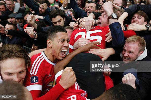 Manchester United's English defender Chris Smalling and Manchester United's English midfielder Jesse Lingard celebrate with the crowd after...
