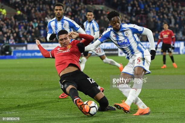 Manchester United's English defender Chris Smalling blocks a shot from Huddersfield Town's Swissborn Dutch defender Terence Kongolo during the...