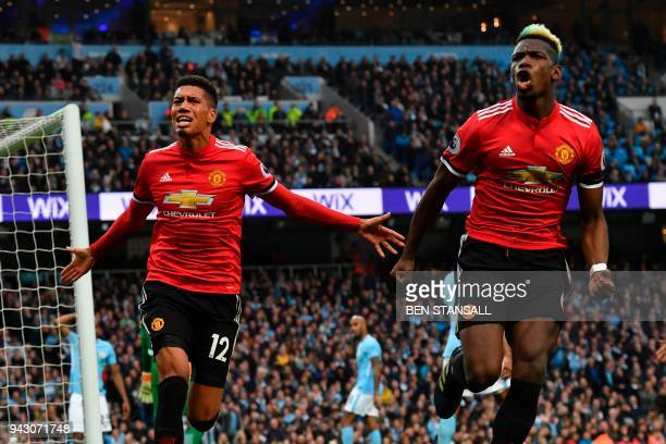 Manchester United's English defender Chris Smalling celebrates scoring their third goal with Manchester United's French midfielder Paul Pogba during...