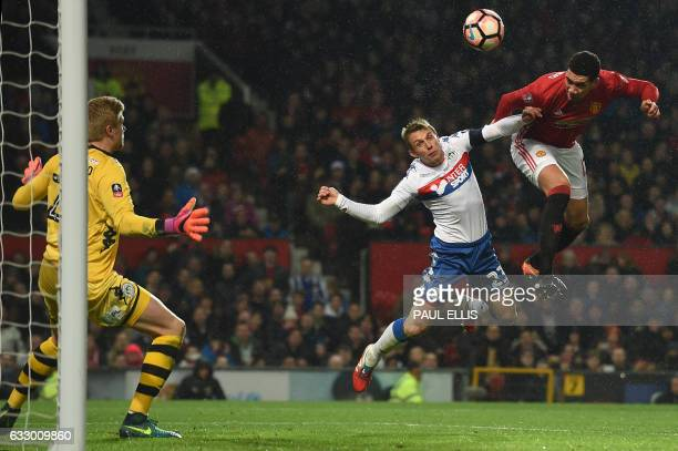 TOPSHOT Manchester United's English defender Chris Smalling heads the ball in to score their second goal during the English FA Cup fourth round...