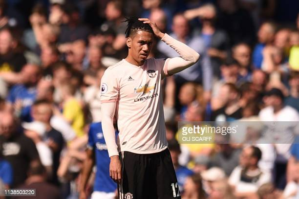Manchester United's English defender Chris Smalling reacts after Everton's fourth goal during the English Premier League football match between...