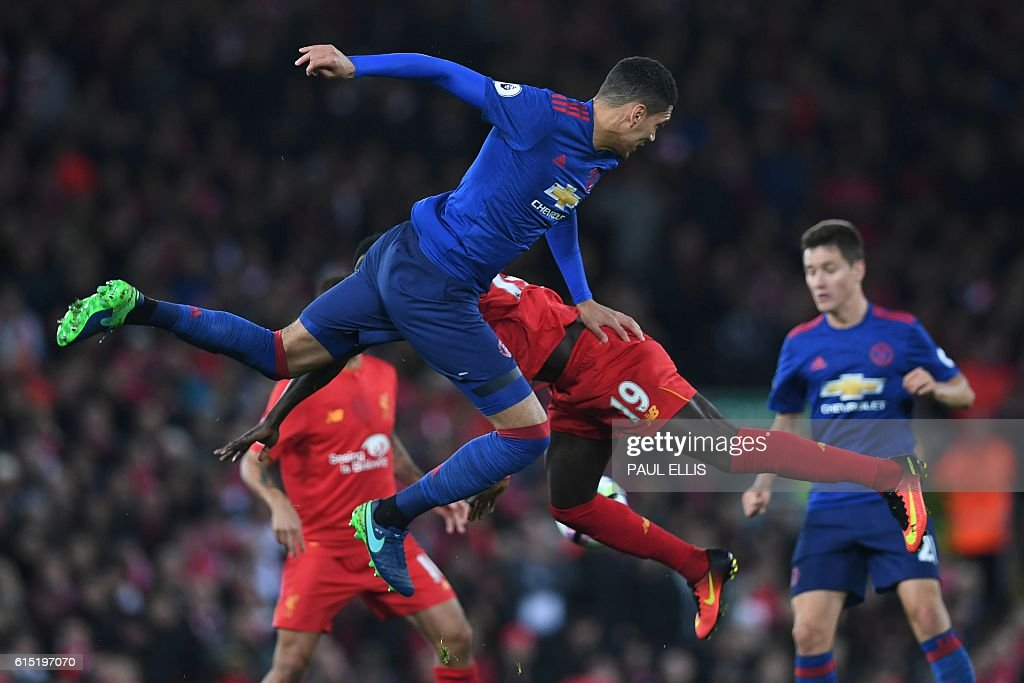 Manchester United's English defender Chris Smalling (L) vies with Liverpool's Senegalese midfielder Sadio Mane during the English Premier League football match between Liverpool and Manchester United at Anfield in Liverpool, north west England on October 17, 2016. / AFP / Paul ELLIS / RESTRICTED TO EDITORIAL USE. No use with unauthorized audio, video, data, fixture lists, club/league logos or 'live' services. Online in-match use limited to 75 images, no video emulation. No use in betting, games or single club/league/player publications. /