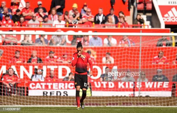 Manchester United's English defender Chris Smalling walks back to the half way line after conceding their second goal during the English Premier...