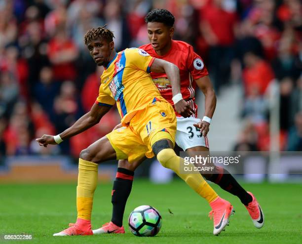 Manchester United's English defender Demetri Mitchell vies with Crystal Palace's Ivorian striker Wilfried Zaha during the English Premier League...