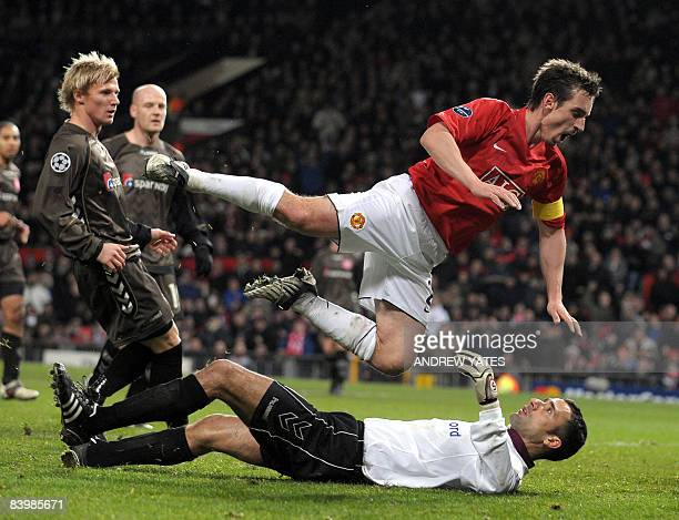 Manchester United's English defender Gary Neville falls over Aalborg's Moroccan goalkeeper Karim Zaza during their UEFA Champions league group E...