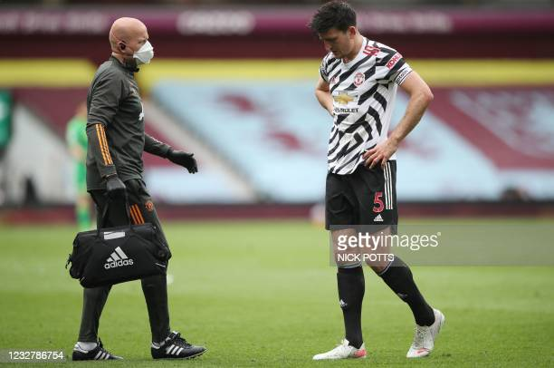 Manchester United's English defender Harry Maguire leaves the pitch with an injury during the English Premier League football match between Aston...