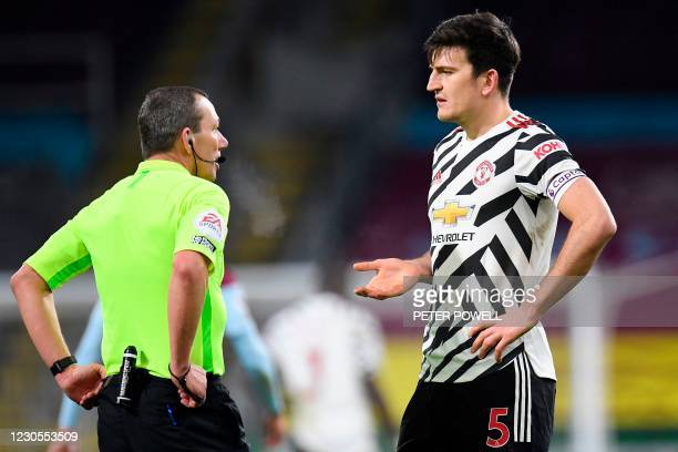 Manchester United's English defender Harry Maguire talks to Referee Kevin Friend at the end of the first half during the English Premier League...