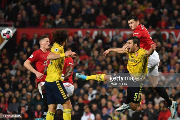 Manchester United's English defender Harry Maguire vies with Arsenal's Greek defender Sokratis Papastathopoulos during the English Premier League...