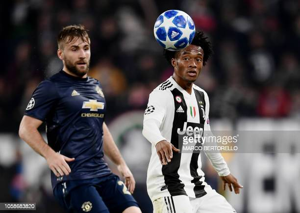 Manchester United's English defender Luke Shaw and Juventus' Colombian midfielder Juan Cuadrado go for the ball during the UEFA Champions League...