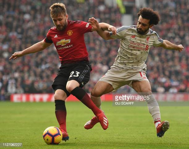 Manchester United's English defender Luke Shaw beats Liverpool's Egyptian midfielder Mohamed Salah during the English Premier League football match...