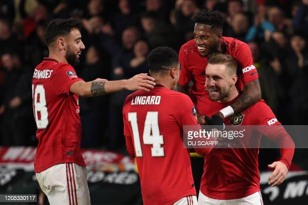 Manchester United's English defender Luke Shaw celebrates scoring his team's first goal with Manchester United's Portuguese midfielder Bruno...