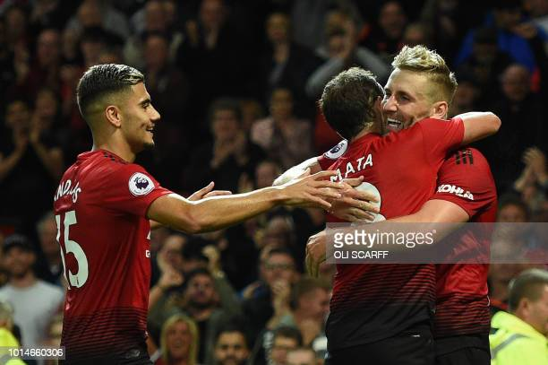 Manchester United's English defender Luke Shaw celebrates with Manchester United's Spanish midfielder Juan Mata and Manchester United's Belgianborn...