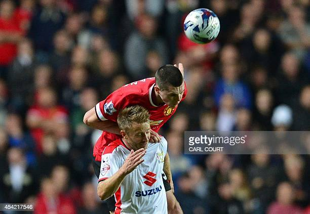 Manchester United's English defender Michael Keane wins a header from MK Dons English midfielder Dean Bowditch during the English League Cup second...