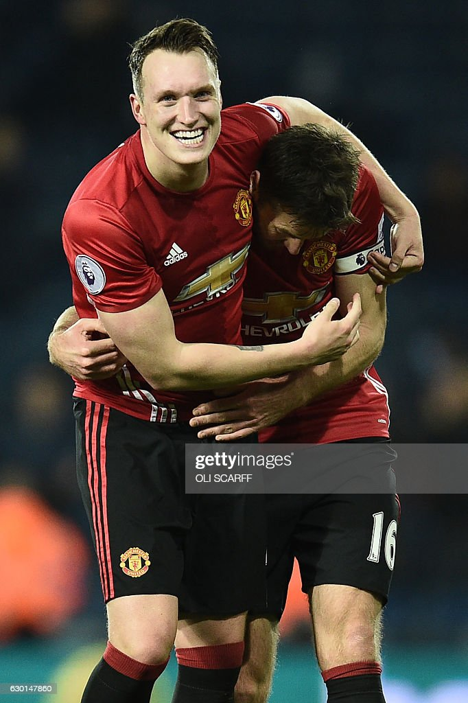Manchester United's English defender Phil Jones (L) and Manchester United's English midfielder Michael Carrick (R) celebrate on the pitch after the English Premier League football match between West Bromwich Albion and Manchester United at The Hawthorns stadium in West Bromwich, central England, on December 17, 2016. Manchester United won the game 2-0. / AFP / Oli SCARFF / RESTRICTED TO EDITORIAL USE. No use with unauthorized audio, video, data, fixture lists, club/league logos or 'live' services. Online in-match use limited to 75 images, no video emulation. No use in betting, games or single club/league/player publications. /